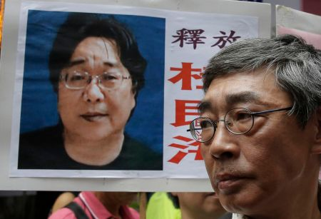 A picture of Hong Kong bookseller Gui Minhai is shown on a placard beside another bookseller, Lam Wing-kee, who criticized Gui's prison sentence announced by China. Kin Cheung/Associated Press/File 2016/Associated Press